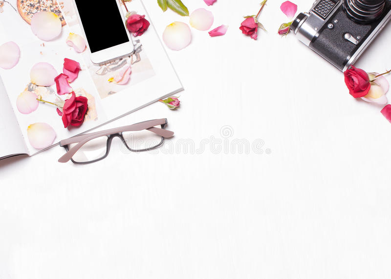 The composition of red roses, petals, magazine, phone, camera. On a white background. Soft focus. View from above. Designer working space concept, creative stock images