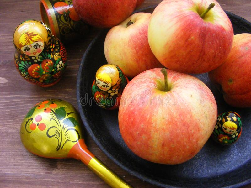 Composition of red and yellow apples on black cast iron plate with traditional russian nesting dolls matrioshka and painted spoon. Composition of apples on black royalty free stock photo