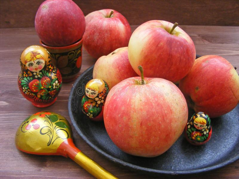 Composition of red and yellow apples on cast iron plate with traditional russian nesting dolls matrioshka and painted spoon on stock images