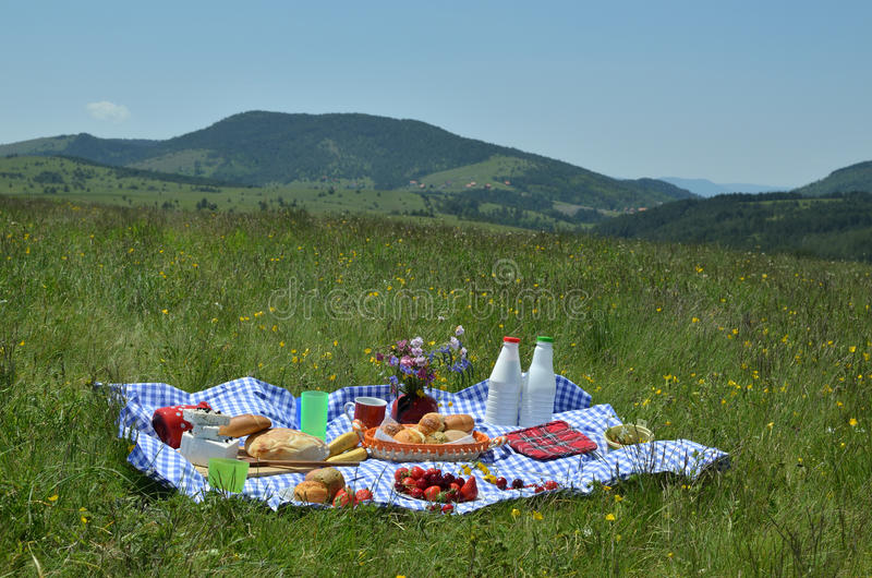 Composition of Rich Picnic Food. With mountain meadow and hills in background stock photo