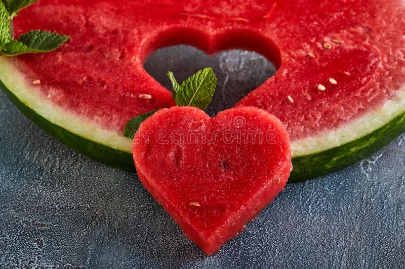 Composition with ripe watermelon, mint leaves and a heart carved in a slice of watermelon. Concept for valentines day. Composition with ripe watermelon, mint stock images
