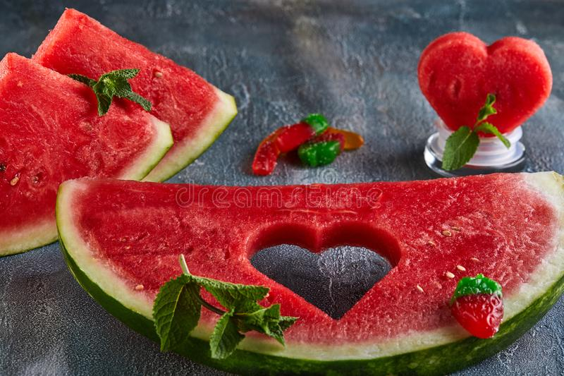 Composition with ripe watermelon, mint leaves and a heart carved in a slice of watermelon. Concept for valentines day. Composition with ripe watermelon, mint royalty free stock photography