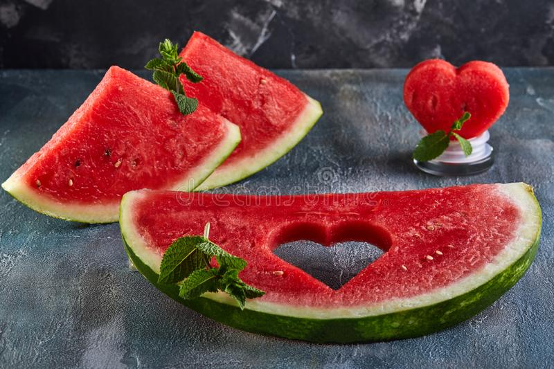 Composition with ripe watermelon, mint leaves and a heart carved in a slice of watermelon. Concept for valentines day. Composition with ripe watermelon, mint stock photography