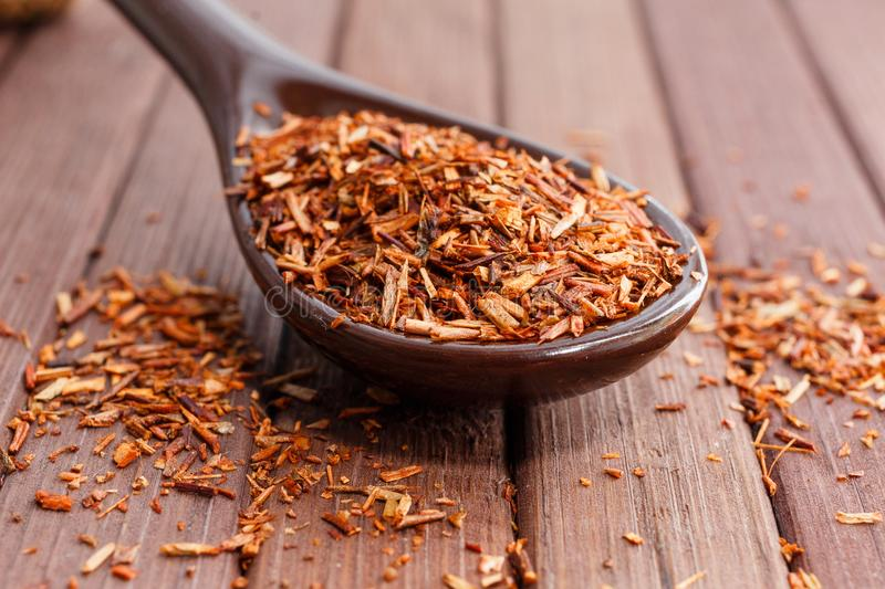 Composition of Rooibos tea is located on a ceramic spoon. Macro royalty free stock photo