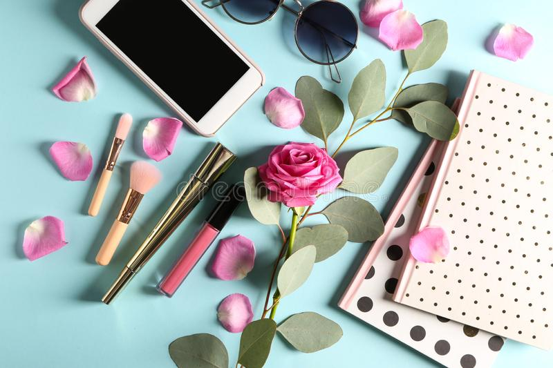 Composition with rose, cosmetics and accessories on blue background royalty free stock photography