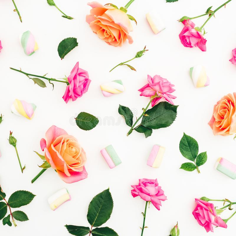 Composition of roses flowers and marshmallow with sugar candy on white background. Flat lay. Top view stock image
