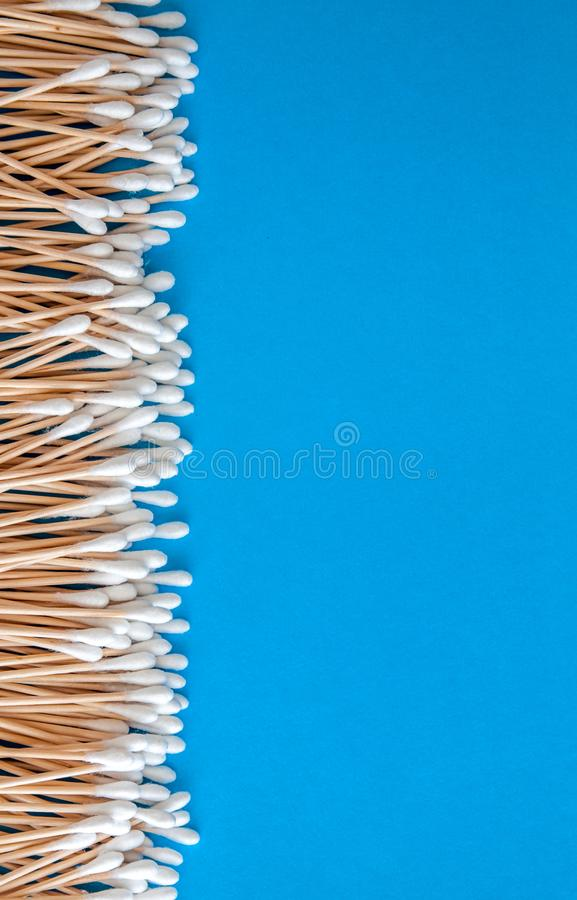 The composition is a round frame of wooden cotton swabs on a blue background and the words natural, eco-friendly. Flat lay. Copy royalty free stock photography