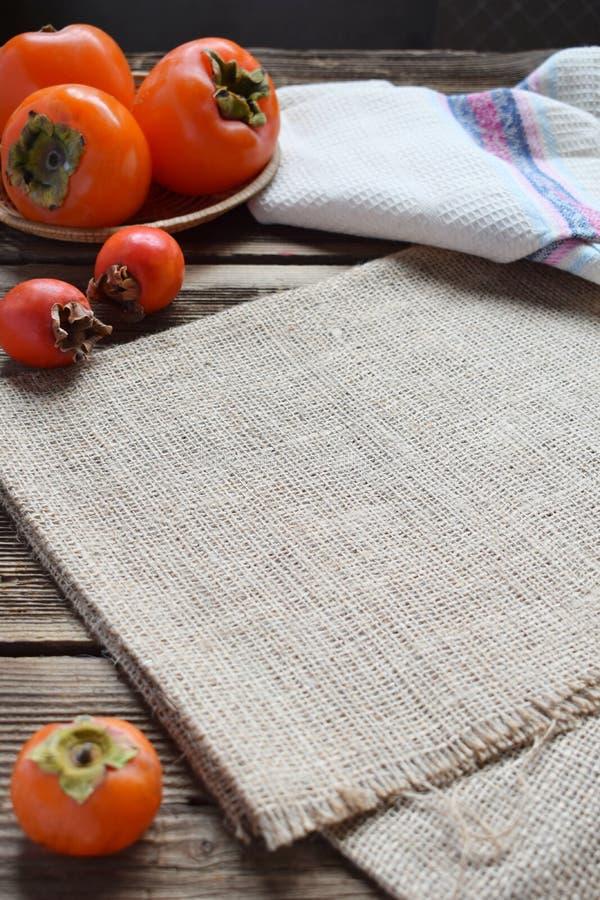 Composition rustique avec différentes variétés de kakis et de planche à découper en bois Style campagnard Faisant cuire au four o image libre de droits