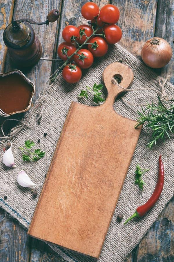 Composition rustique avec le conseil en bois, le moulin de poivre, le souce de tomate, les herbes fraîches, les légumes et les ép photographie stock