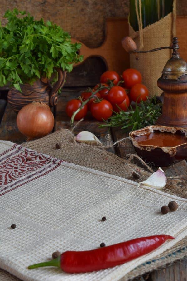 Composition rustique avec le moulin de poivre, le souce de tomate, les bouteilles de vin, les verts, les légumes et les épices St image stock