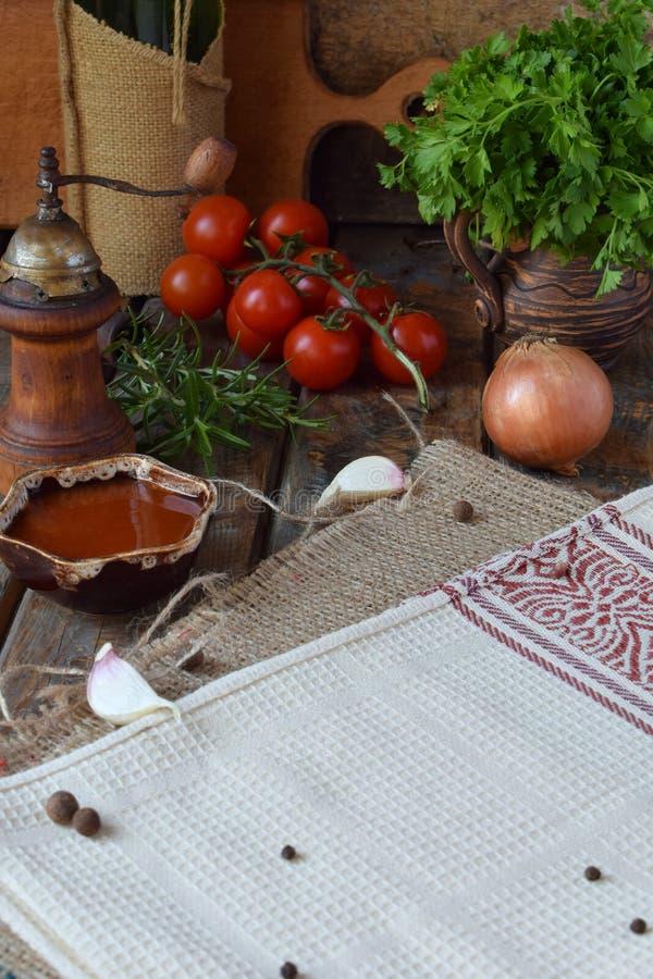 Composition rustique avec le moulin de poivre, le souce de tomate, les bouteilles de vin, les verts, les légumes et les épices St photographie stock