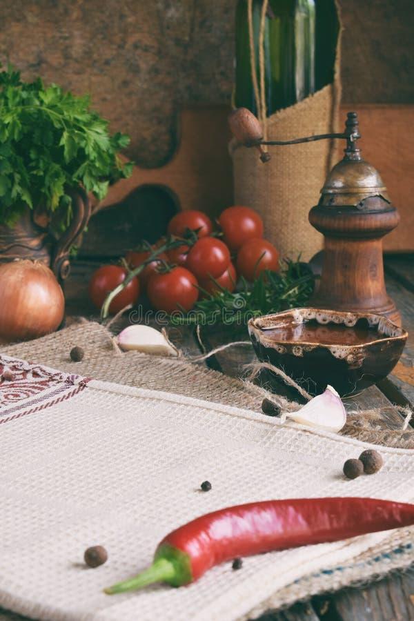Composition rustique avec le moulin de poivre, le souce de tomate, les bouteilles de vin, les verts, les légumes et les épices St photos libres de droits