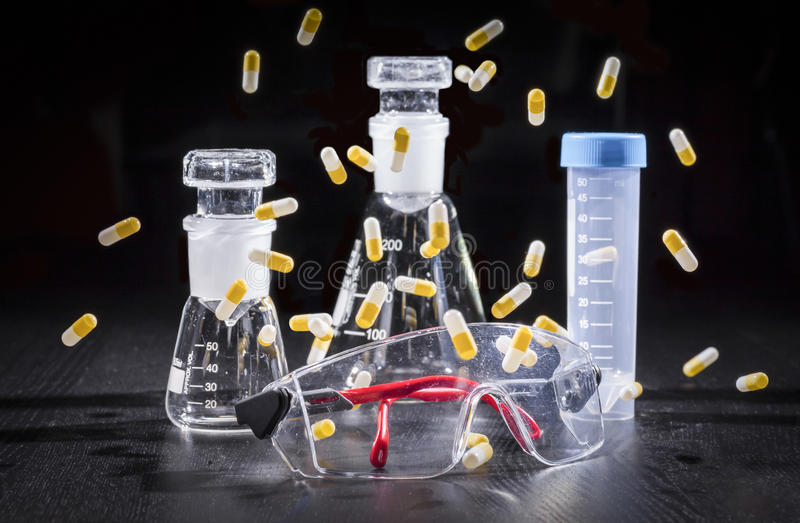 Composition: safety glasses, chemical glassware and capsules. Composition with safety glasses, chemical laboratory glassware and white and yellow falling stock images