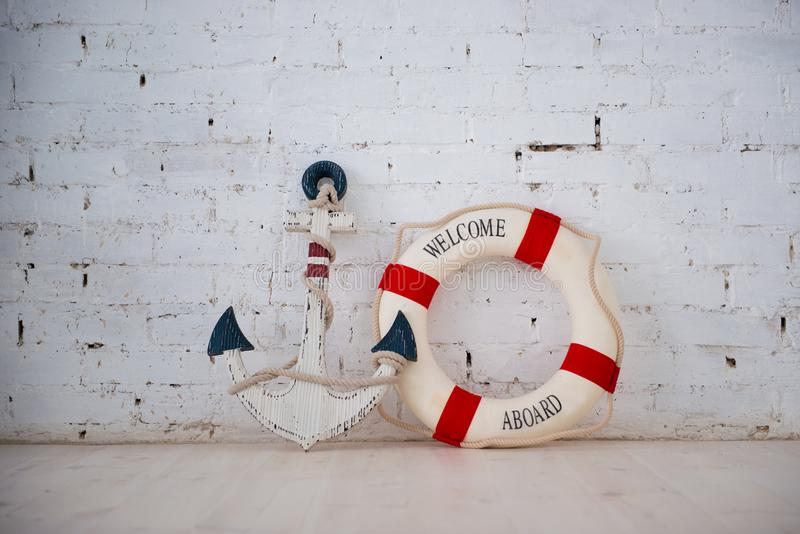 A composition on a sea theme with an anchor and life ring on a white brick wall. stock photography