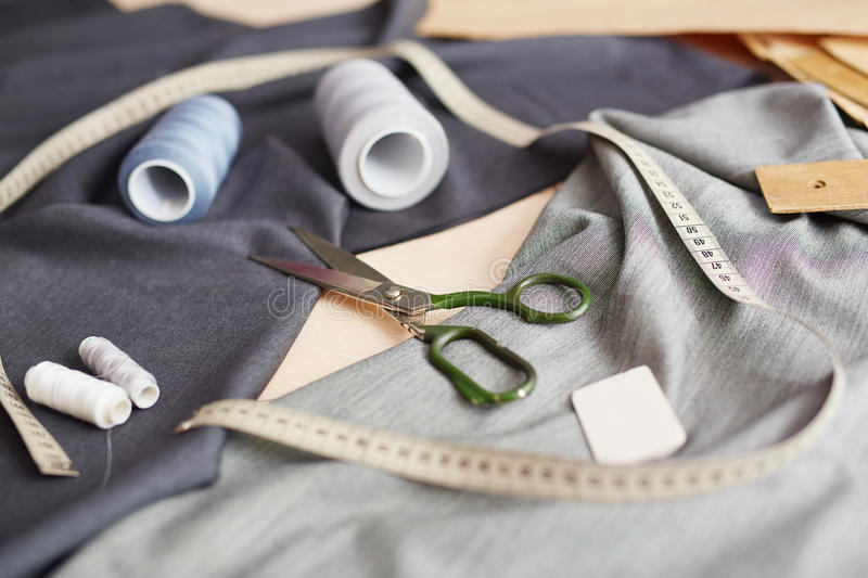 Composition of Sewing Tools on Table. Closeup image of different sewing items on tailors working table: scissors, measuring tape and thread spools stock images