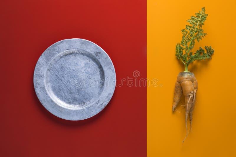 Composition simpliste de carotte organique et de plat argenté rustique image stock