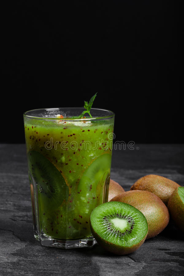 A freshly squeezed sweet cocktail from kiwi with mint on a stones desk and on a black background. Organic fruits. stock photo