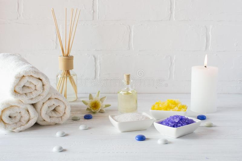 Composition of spa wellness products on white background. with towel,white lily, sea salt, bath oil, sugar body scrub stock photography