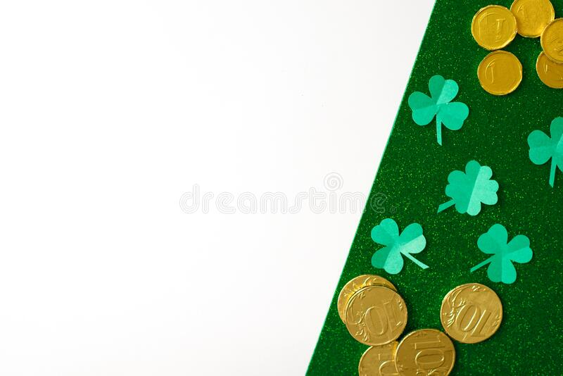 The composition of the St. Patrick`s day. Leaves of paper clover and gold coins on a green shiny and white background stock image