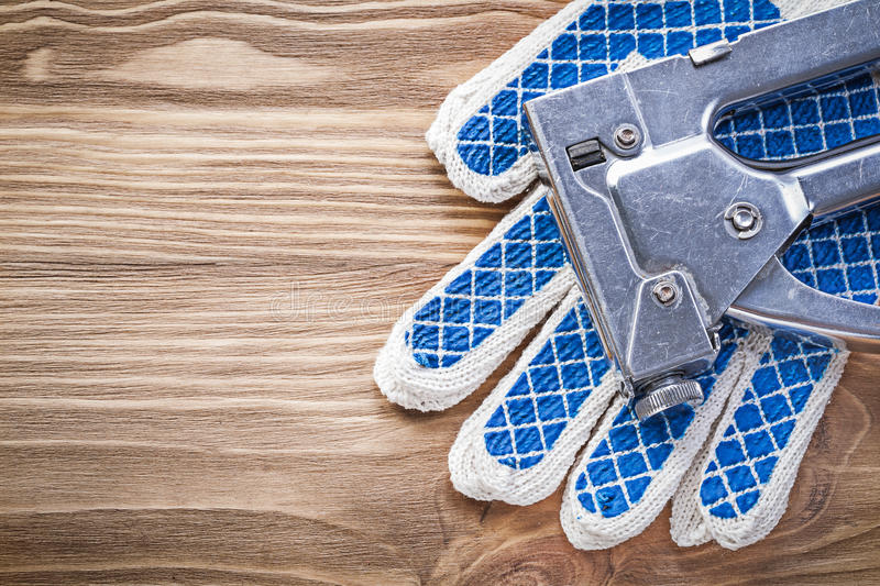 Composition of staple gun working safety gloves on wooden board.  royalty free stock images