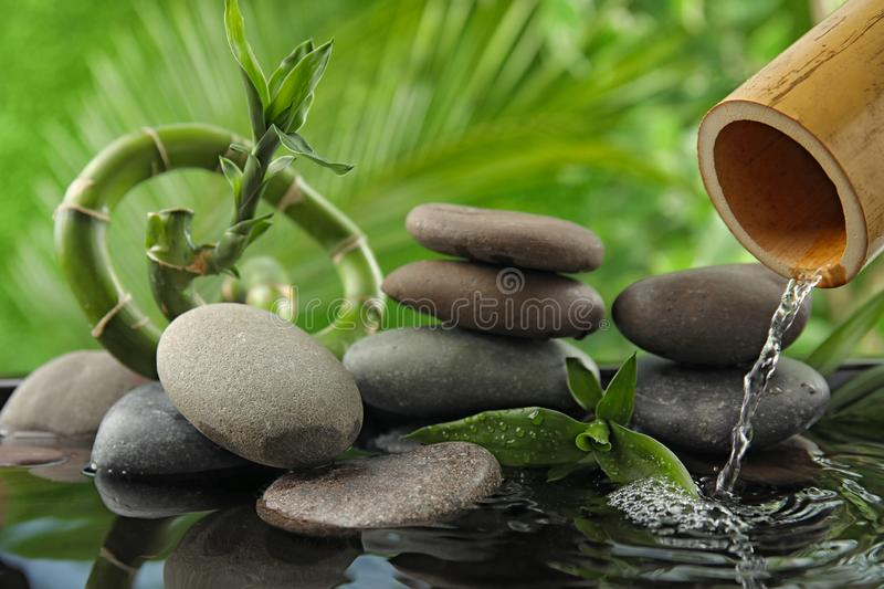 Composition with stones and bamboo fountain against background. Zen concept stock photos