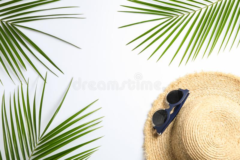 Composition with straw hat, sunglasses and palm leaves on white background. Top view. Space for text royalty free stock image