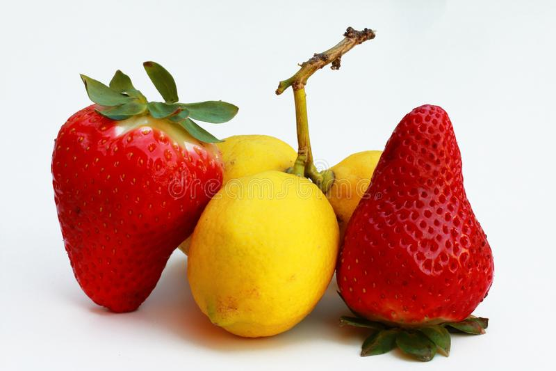 Huge strawberries along with small lemons stock photography