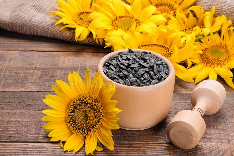 Sunflower seeds in a wooden crush and sunflower flowers on a brown wooden table. Composition with sunflower seeds in a wooden crush and sunflower flowers on a royalty free stock image