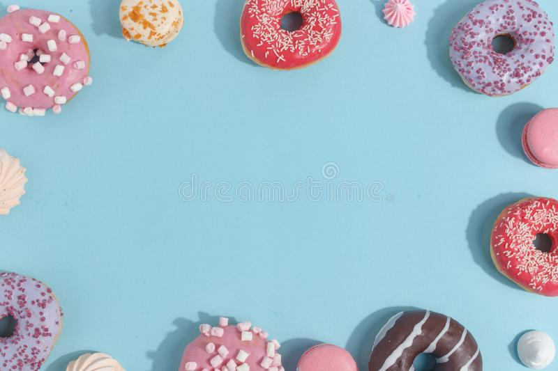 Composition of sweet glazed donuts and sweets on a blue background. Top view. Concept of children's holiday. Space for copy royalty free stock image