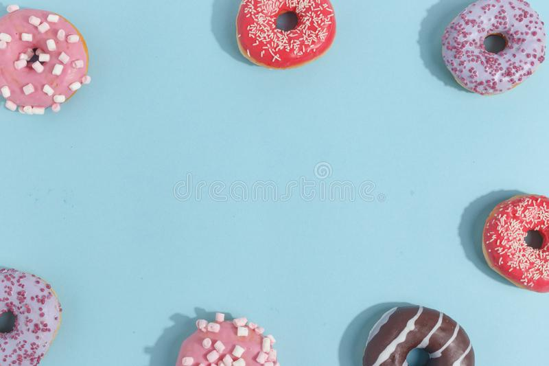 Composition of sweet glazed donuts and sweets on a blue background. Top view. Concept of children's holiday. Space for copy. Dessert food sprinkles stock images
