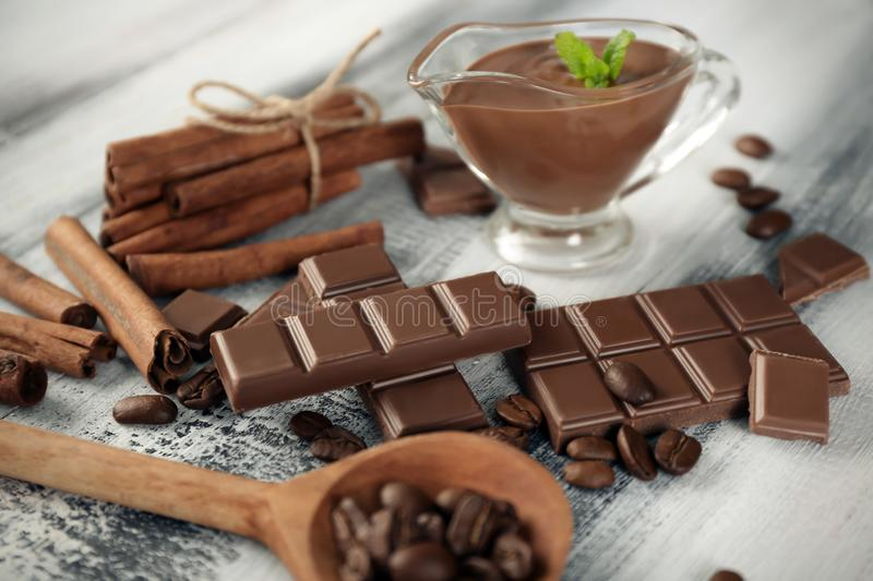 Composition with tasty chocolate, cinnamon sticks and coffee beans on wooden background royalty free stock image