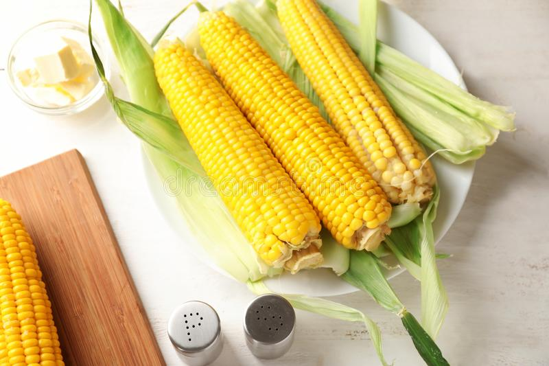 Composition with tasty corn cobs on wooden table royalty free stock photo