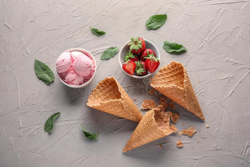 Composition with tasty ice cream, strawberries and waffle cones on light table stock image
