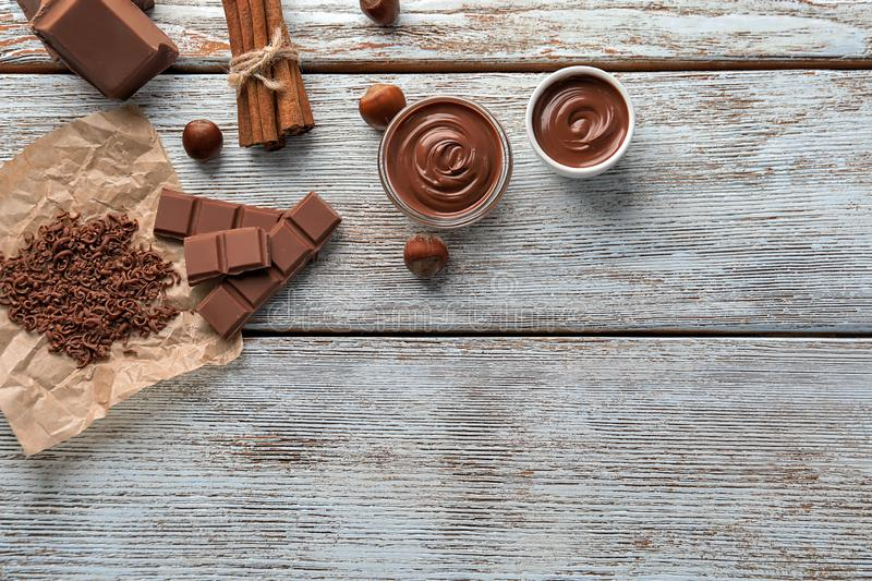 Composition with tasty melted and solid chocolate on wooden background stock photo