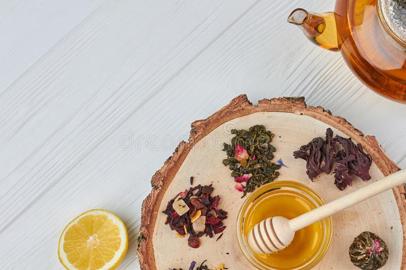 Composition with tea and honey on wooden background. Wooden stump with assorted dry tea, honey, lemon and teapot stock photo