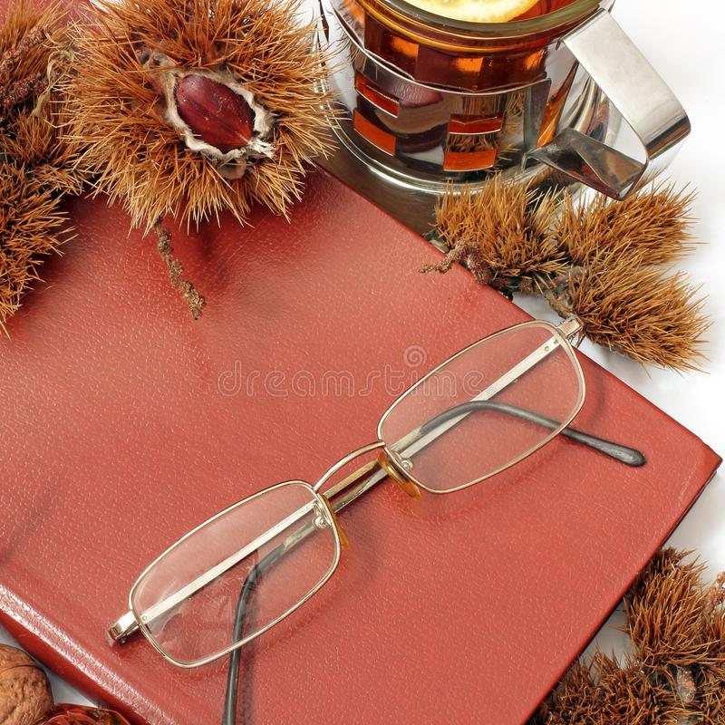 Composition. Tea with lemon, a closed book, glasses and chestnuts royalty free stock images