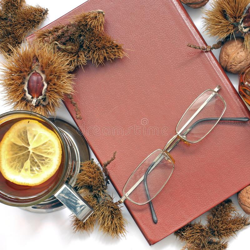 Composition. Tea with lemon, a closed book, glasses and chestnuts stock photos