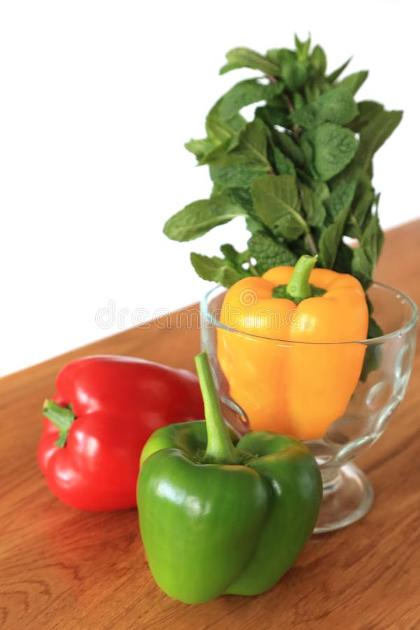 Composition with three color - red, green, yellow fresh sweet pepper or bell pepper on wooden background.  royalty free stock images