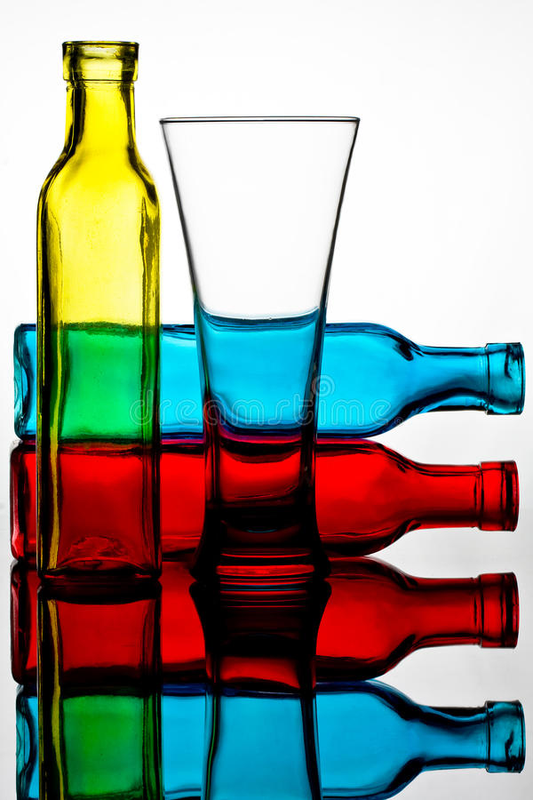 Coloured Bottles and Glass Reflected in a Mirror royalty free stock photo