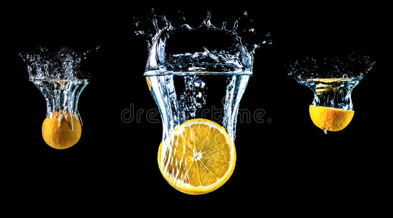Composition of three oranges falling into water close-up, macro, splash water, bubbles, isolated, black background. stock images