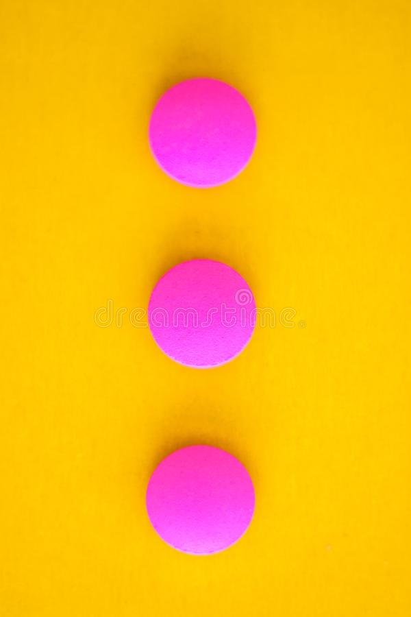 Composition of three pink round pills on a yellow background. Flat lay. Copy space. Trend Close-up stock photography