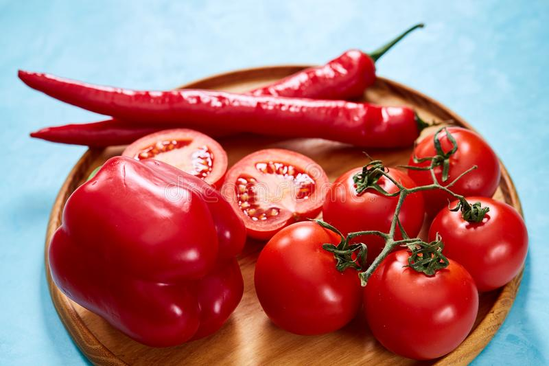 Composition of tomato bunch and halves and sweet pepper on wooden plate, top view, close-up, selective focus. royalty free stock photo