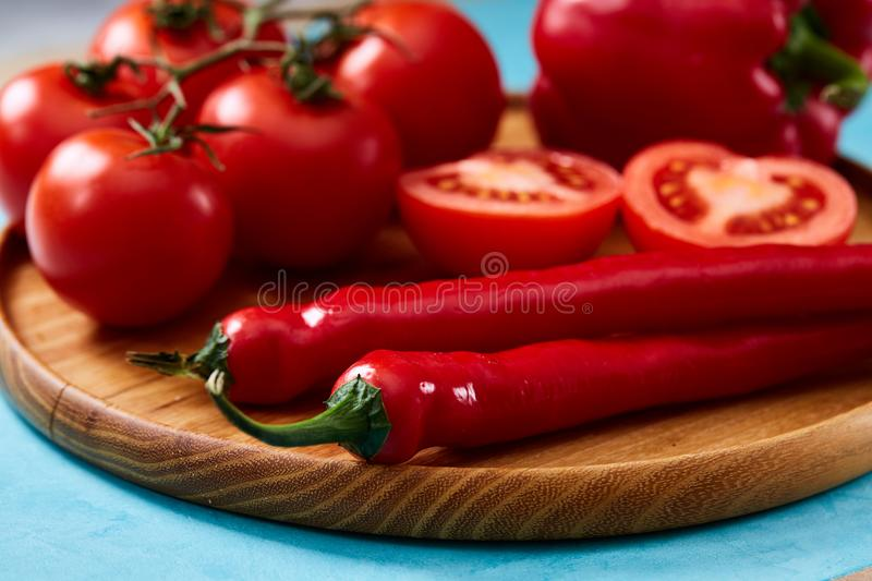 Composition of tomato bunch and halves and sweet pepper on wooden plate, top view, close-up, selective focus. royalty free stock image