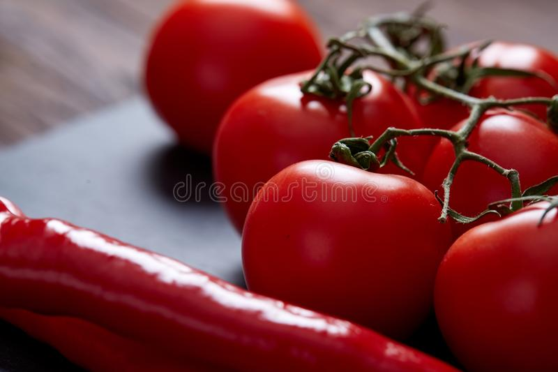 Composition of tomato bunch and hot pepper on black piece of board, top view, close-up, selective focus. stock photo