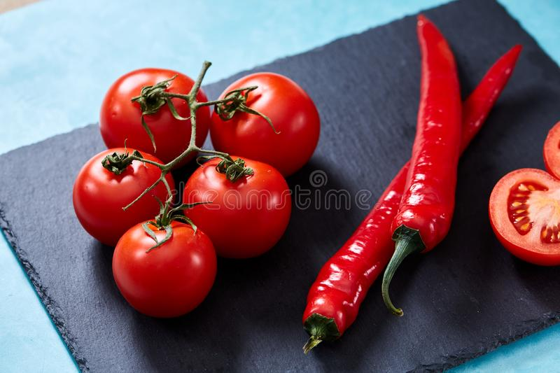 Composition of tomato bunch and sweet pepper on black piece of board, top view, close-up. stock photography