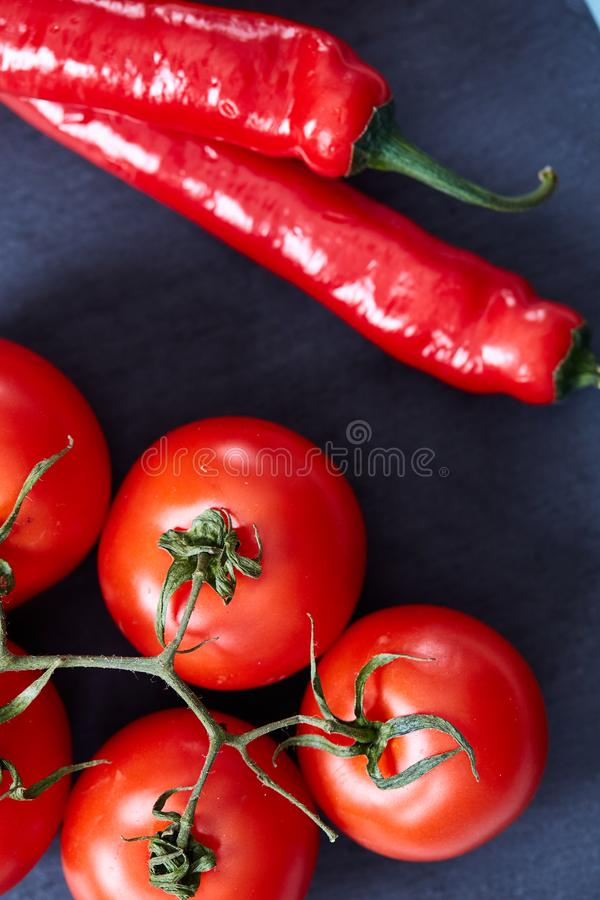 Composition of tomato bunch and sweet pepper on black piece of board, top view, close-up. stock photos