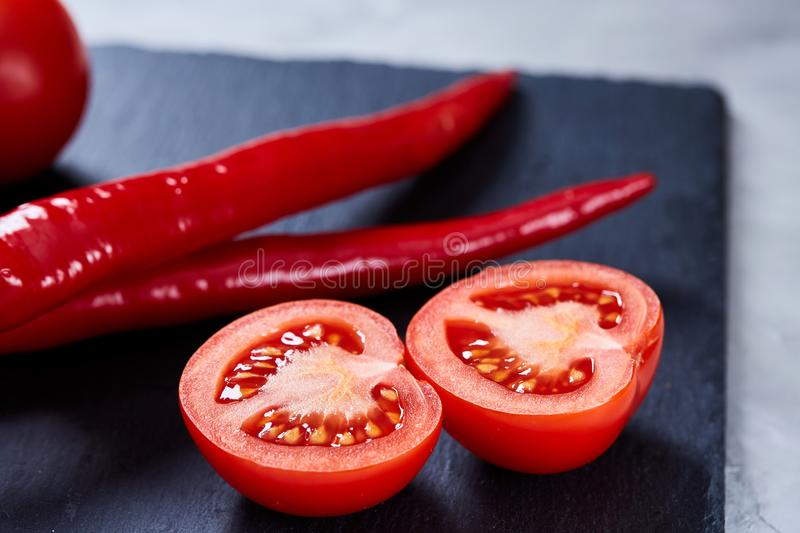 Composition of tomato bunch and sweet pepper on black piece of board, top view, close-up. royalty free stock photography