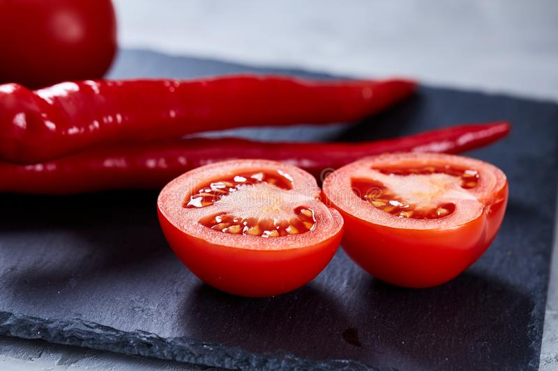 Composition of tomato halves and sweet pepper on black piece of board, top view, close-up, selective focus. stock photo