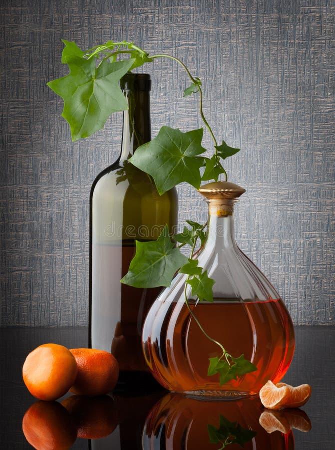 Composition toujours en vie avec des feuilles et des mandarines de bouteilles sur l'obscurité photographie stock libre de droits