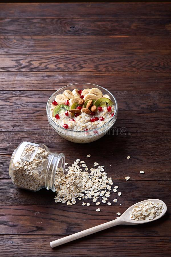 Composition with bowl of oatmeal porrige and dry oatmeal in glassware on vintage wooden table, selective focus stock images